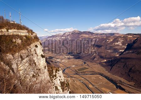Aerial view of the Adige Valley in winter with the highway and cultivated fields and the plateau of Lessinia on background Veneto Italy