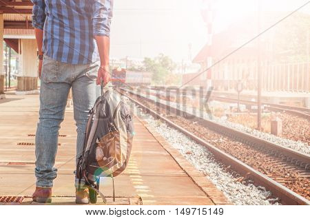 Male tourists are carrying luggage waiting train on the platform. Photo light and adjustable tone vintage