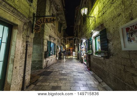 KOTOR MONTENEGRO - 13TH AUGUST 2016: A view along streets of Kotor at night. The outside of shops and people can be seen.