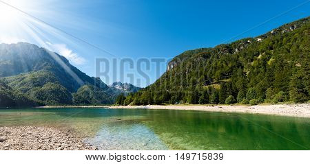 Lago del Predil (Predil Lake). Small mountain lake in Julian Alps with sun rays Tarvisio Friuli Venezia Giulia Italy
