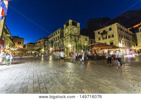 KOTOR MONTENEGRO - 13TH AUGUST 2016: Views along streets of Old Town Kotor at night. The outside of buildings restaurants and people can be seen.