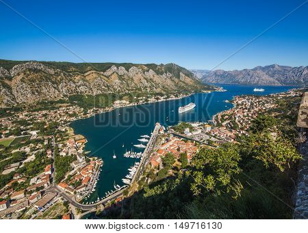 High angle view of Kotor Bay during the day in the summer. Mountains cruise ships other boats and buildings can be seen.