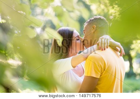 Multi ethnic couple kissing among trees - photographed through leaves