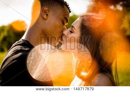 Young mixed race couple kissing outdoor in nature with orange flare reflections
