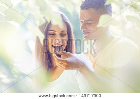 Young man feeding her girl with chocolate outdoor in nature - soft tone