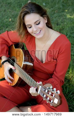 Casual girl dressed in red playing guitar on the park