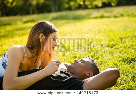 Woman holding stem and playing with it on man's face - couple on date in nature