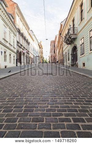 ZAGREB CROATIA - 17TH AUGUST 2016: A view along streets in Zagreb showing the outside of buildings and cobbled streets. A person can be seen.