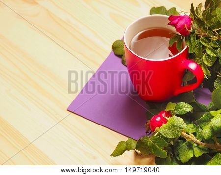 Red cup of hot tea with leaves and rose hips.