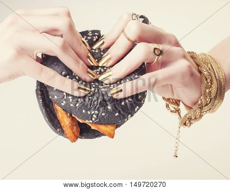 hands of rich woman with golden manicure and jewelry holding black hamburger close up fashion concept