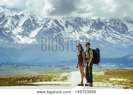 Couple of backpackers hitchhiking on the road on mountains backdrop