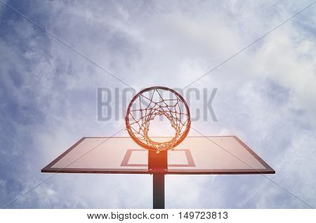 Basketball hoop with net and cloud background.