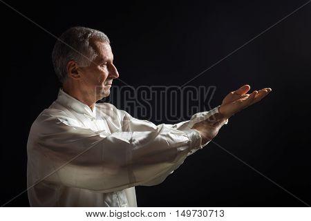 Senior man enjoys exercise Tai Chi indoor.