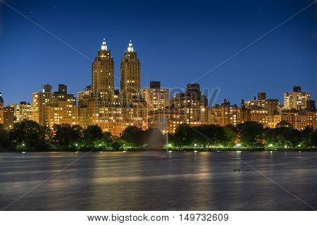 Upper West Side and Central Park Reservoir at twilight. Long exposure reveals star trails and accentuates building lights. Manhattan, New York City