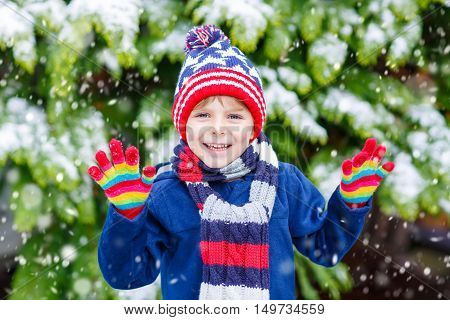Winter portrait of little kid boy in colorful clothes, outdoors during snowfall. Active outoors leisure with children in winter on cold snowy days. Happy child having fun with snow