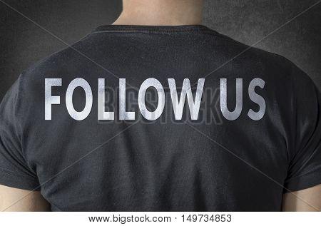FOLLOW US tittle on black t-shirt. Back view.