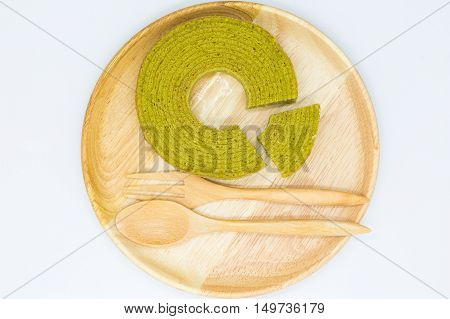 Multiple layer round green tea cake on wooden disk, on white background