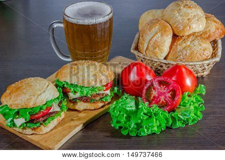 Closeup of beer and home made burgers on sesame buns with beef patties and fresh salad ingredients on wooden background