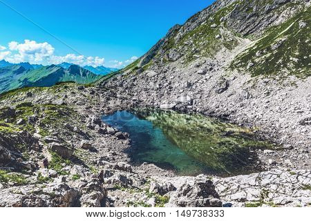 Stagnant pool of water near mountain top during the summer in Allgau, Germany, Europe