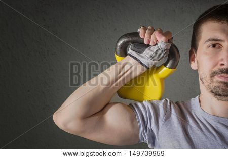Male athlete lifting kettle bell. Workout and healthy lifestyle concept.