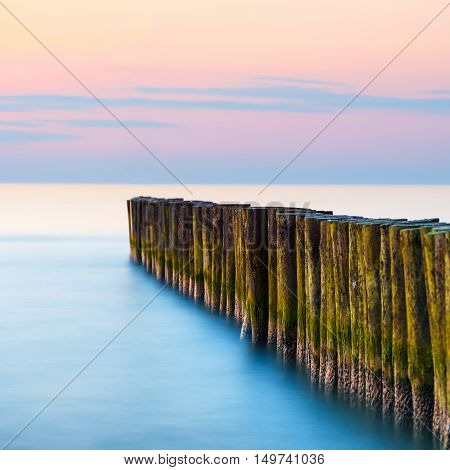 sunset on the beach with a wooden breakwater long exposure