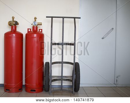 fire extinguishing system in the office. fire cylinders and transport trolley stand by the wall in an office building