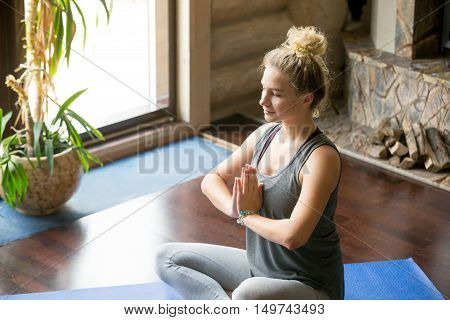 Close-up portrait of attractive young woman working out at home, doing yoga exercise on blue mat, sitting in Easy Decent, Pleasant Posture with palms in Namaste, meditating, breathing, relaxing