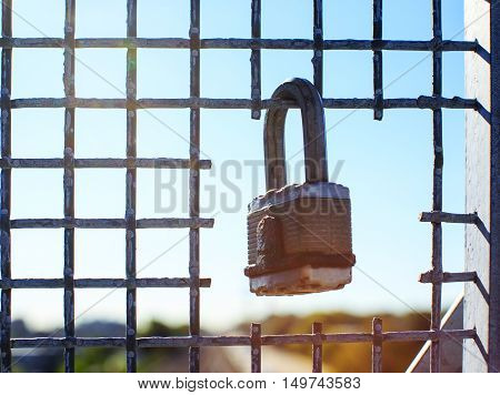 lock on the grid against a blue sky. padlock hanging in the lattice opening. the concept of freedom
