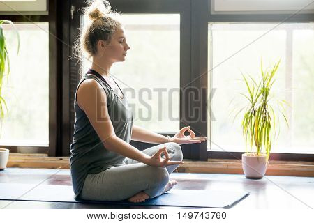 Attractive young woman working out at home, doing yoga exercise on blue mat, sitting in Easy Decent, Pleasant Posture , meditating, breathing, relaxing with closed eyes. Full length. Side view