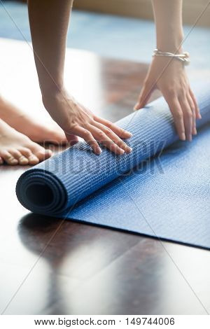 Close-up of attractive young woman folding blue yoga or fitness mat after working out at home in living room. Healthy life, keep fit concepts. Vertical image