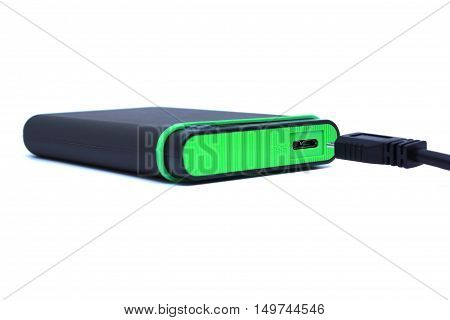 green external hard-ish is plugging in with the cable on white isolated