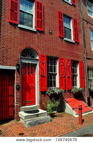 Philadelphia Pennsylvania - June 25 2013: 18th century colonial brick home built in 1752 with red fan doorway on historic Elfreth's Alley