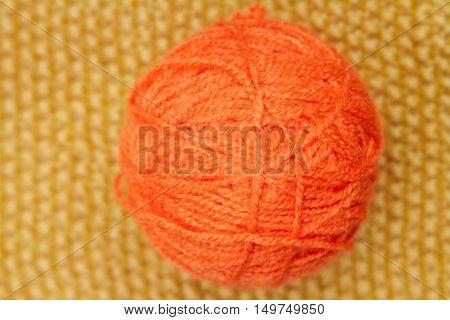 Orange Ball Of Wool On Yellow Cloth Woven Wool