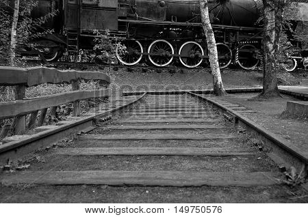 End of Train tracks against old steam locomotive in black and white photo