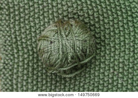 Green Ball Of Wool On Green Cloth Woven Wool