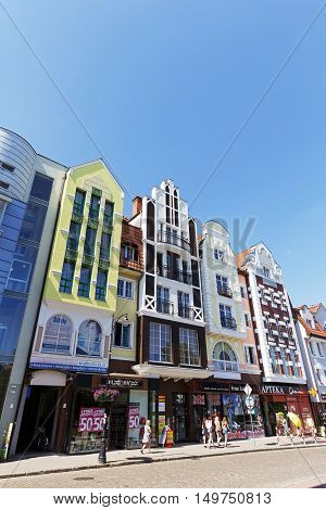 KOLOBRZEG POLAND - JUNE 23 2016: Narrow and tall buildings of colorful apartment houses whose facades have been recently renovated together with shops on the ground floor are a tourist attraction