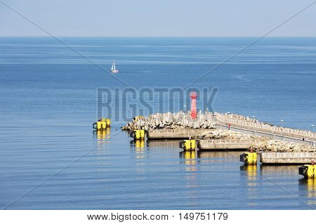 KOLOBRZEG POLAND - JUNE 22 2016: The eastern breakwater of the seaport equipped with red signal navigation lantern it is part of a reconstructed in 2012 port infrastructure