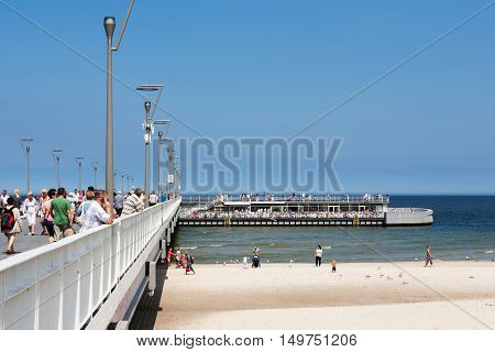 KOLOBRZEG POLAND - JUNE 19 2016: Unidentified tourists strolling along the pier and watch the views the restaurant is located at the end of the jetty where a lot of people enjoy the summer