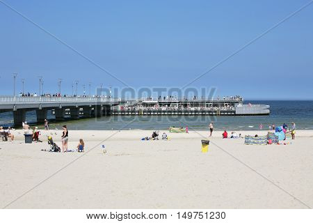 KOLOBRZEG POLAND - JUNE 19 2016: Unidentified tourists enjoy a sunny day on the sandy beach and the others have their coffee time at the cafe located at the end of the pier