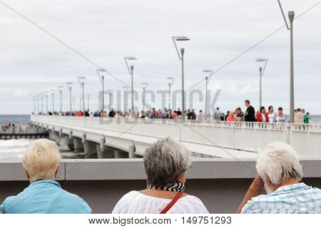 KOLOBRZEG POLAND - JUNE 26 2016: Unidentified tourists enjoy their summer time and are watching the people walking along the reinforced concrete pier by the sea