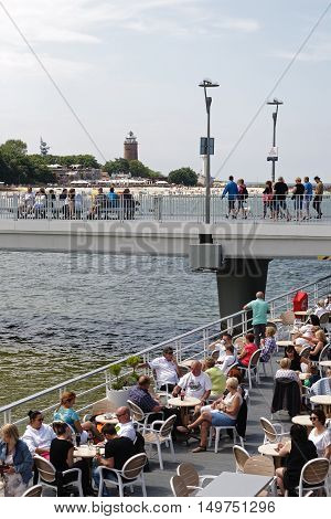 KOLOBRZEG POLAND - JUNE 19 2016: Unidentified tourists enjoy the restaurant placed at the end of the concrete pier other people are resting or are walking along the jetty
