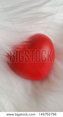 Red heart on a white faux fur background