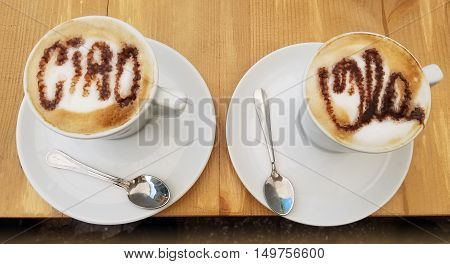 Delicious cappuccino coffee cups with creamy froth greetings design