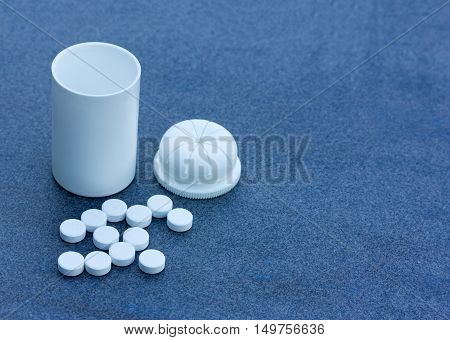White Pills scattered across a Blue Background and an Open Bottle. Top View Closeup. With Space For Your Text