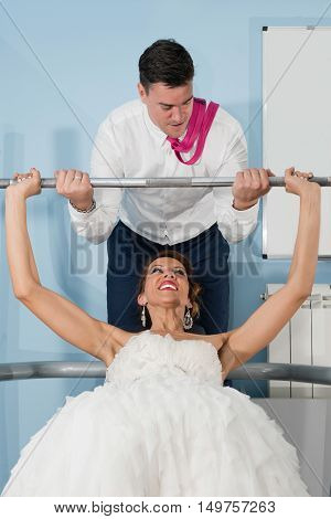 Bride on bench press and groom helping her