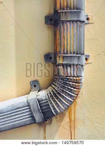 Drain aluminum with stained rust installed on the wall of the building