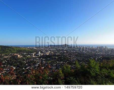 Diamondhead and the city of Honolulu Kaimuki Kahala and oceanscape on Oahu on a nice day at viewed from high in the mountains with trees in the foreground. January 2016.
