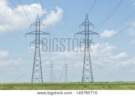 tall twin hydro towers with power lines running across the wide open prairie under a beautiful blue sky with white clouds in the summer time