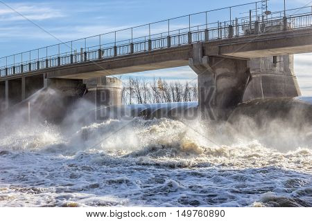 horizontal image of a concrete bridge over a water dam with water running so fast over the turbine it churns violently and splashes down the river in the summer time.