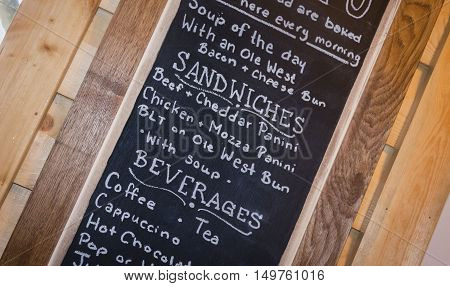 horizontal image of a slanted image of a menu written on a black chalkboard